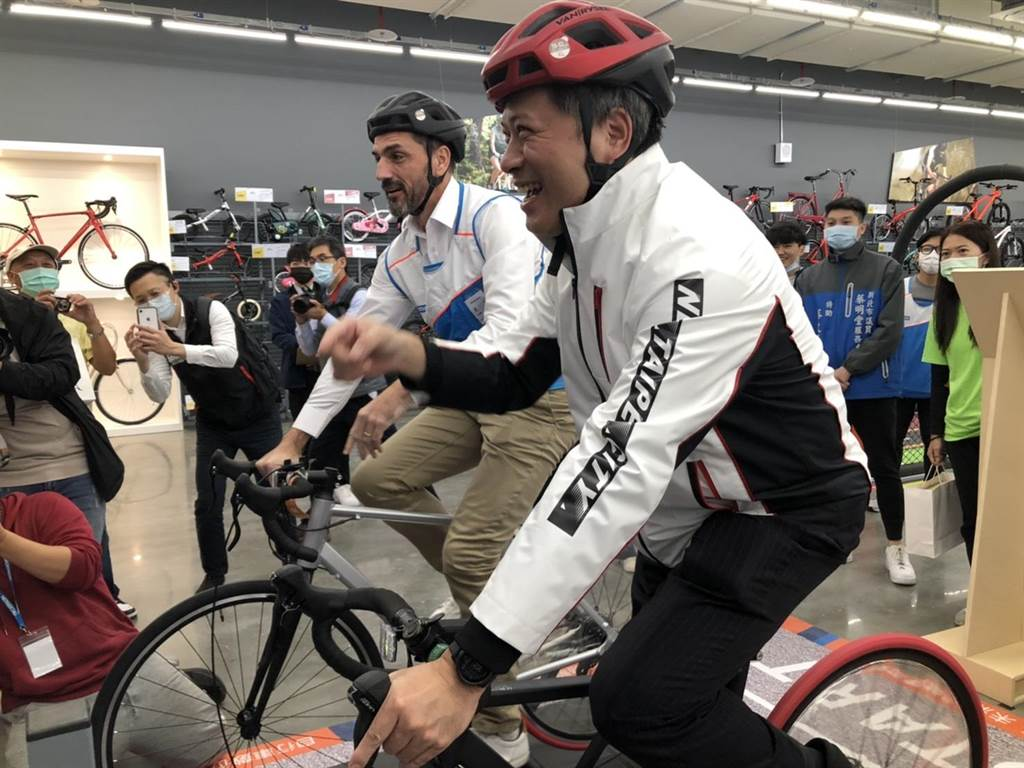 副市長吳明機進入店內體驗時下年輕人最流行的公路車虛擬競速。(李俊淇攝)