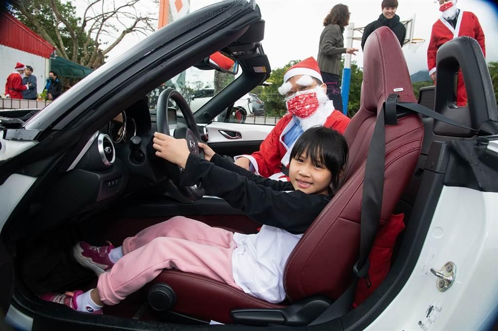 靜浦國小學生興奮地與MAZDA MX-5合影留念,並由MAZDA MX-5與MAZDA CX-30所組成的聖誕麋鹿車隊,載著全校師生體驗乘風的喜悅。