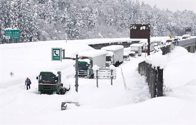 日本靠日本海側地區受到強烈冷氣團影響降下大雪,有約1000輛汽車卡在積雪的高速公路動彈不得,有駕駛靠吃雪止飢,另有3人因身體不適被送醫治療。(圖/路透)