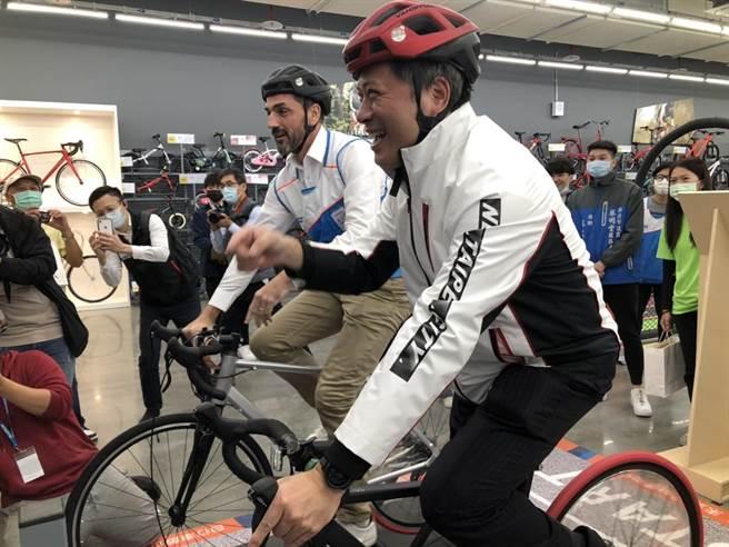 副市长吴明机进入店内体验时下年轻人最流行的公路车虚拟竞速。(李俊淇摄)