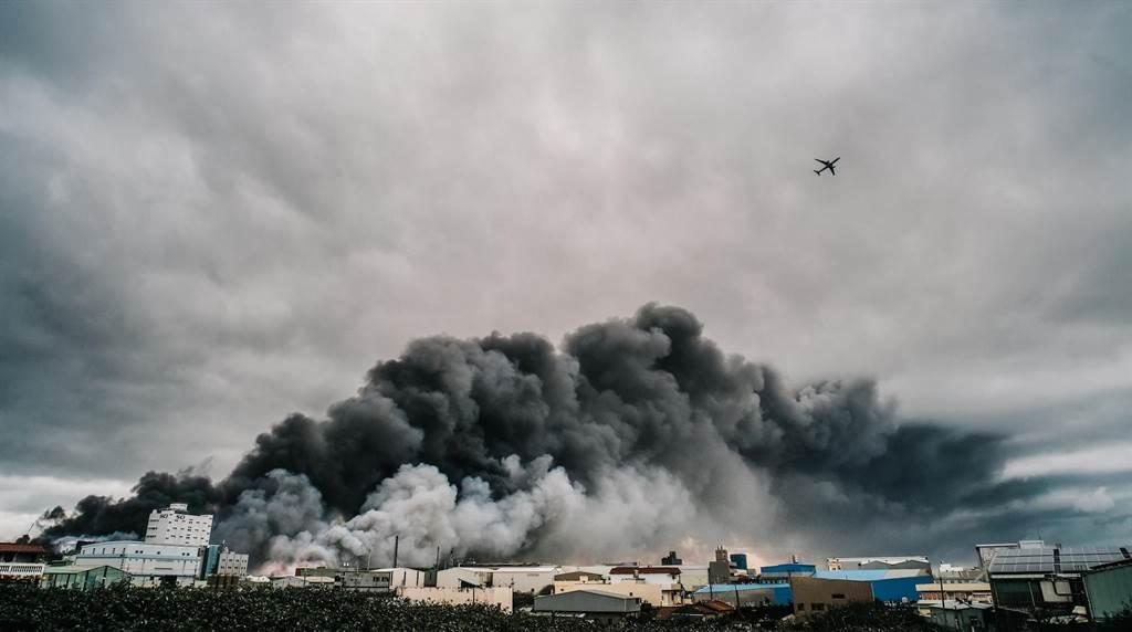 工廠爆炸後引發的一大片濃濃黑煙直竄天際,盤踞桃園國際機場北側跑道上,班機只好穿越濃煙起飛。(郭吉銓攝)