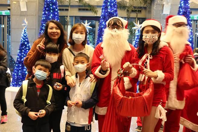 市府同仁裝扮成聖誕老公公及耶誕女郎發放糖果。(許哲瑗攝)