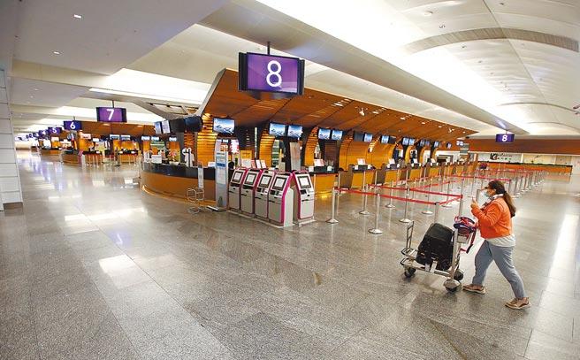 受新冠肺炎疫情影響,航空及觀光相關產業嚴重受創,來台旅遊觀光客人數屢創新低,在桃園機場第一航廈中,1位旅客走過空蕩蕩的出境大廳。(范揚光攝)