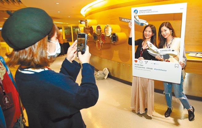 星宇航空「台北-台南雙城號」微旅行班機19日啟航,登機前旅客開心在候機室拍照打卡。(范揚光攝)