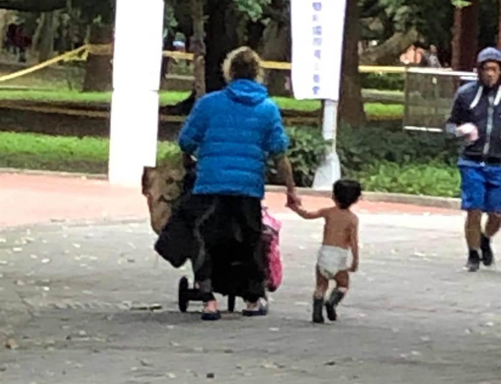 民眾昨(20日)目擊一位爸爸自己身穿羽絨衣,但牽著的兒子卻只包著尿布。(臉書社團《我是永和人》/蘇育宣翻攝)