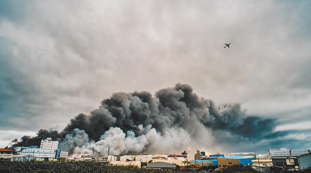 旭富工廠爆炸後引發的一大片濃濃黑煙直竄天際,盤踞桃園國際機場北側跑道上,班機只好穿越濃煙起飛。(郭吉銓攝)