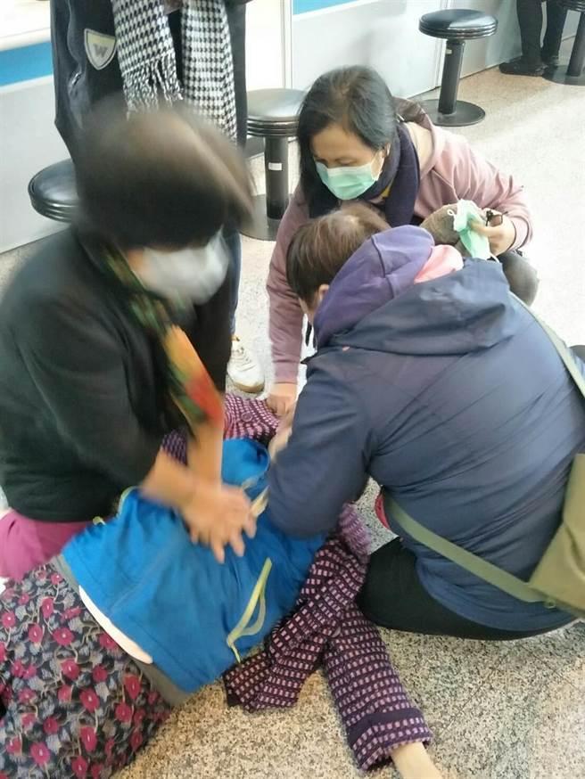 輪椅婦三重公所洽公突暈倒失去生命跡象,公所人員奮力急救。(戴上容翻攝)
