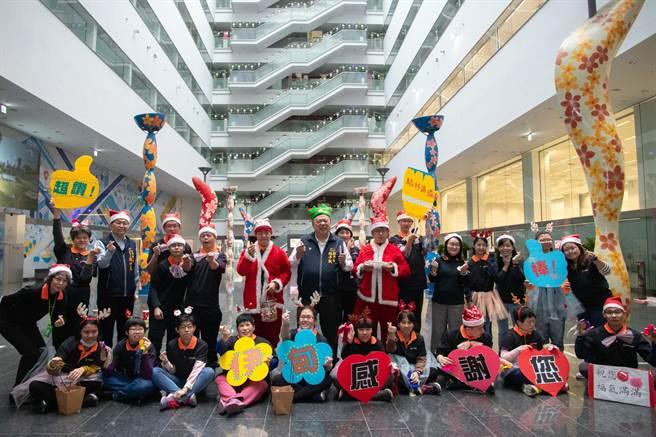 台中市副市長陳子敬21日頭戴名為「永不放棄」的造型耶誕帽,歡迎「樂愛」小作所的身心障礙學員,一起來報佳音。(盧金足攝)