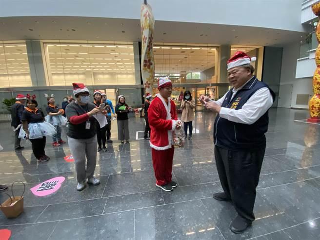 伊甸「樂愛」小作所學員到台中市政府,人人頭上戴著耶誕帽,學員發送糖果傳遞節慶歡樂氣氛。(盧金足攝)