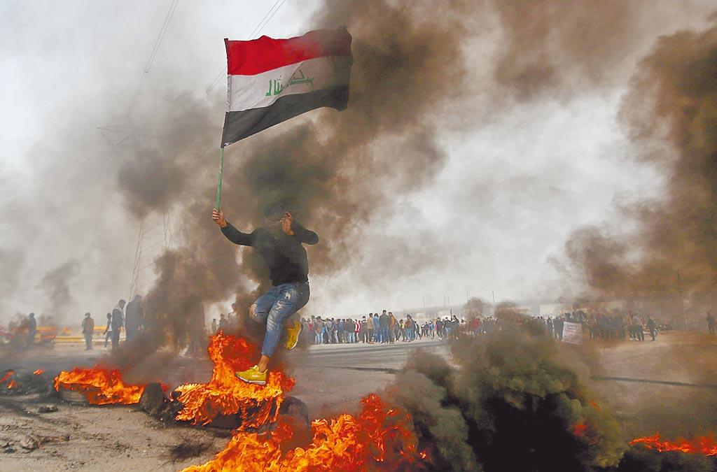 伊拉克反政府人士在南部石油重鎮巴斯拉舉行抗議,焚燒輪胎。(路透)