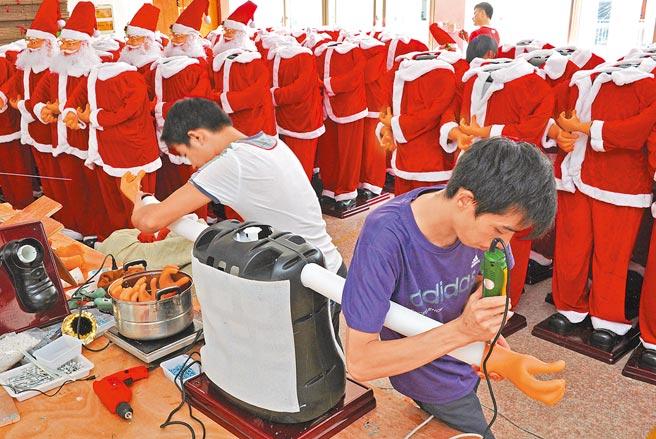 義烏一家聖誕用品企業,兩位工人組裝準備出口的聖誕老人。(新華社資料照片)
