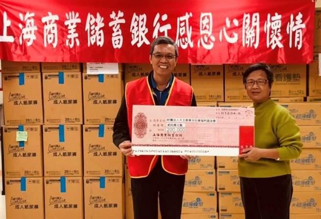 (上海商銀資深副總經理彭國貴(左)代表該行捐贈20萬元支票及物資,由華光秘書處副主任鄒佳蓉代表接受。圖/上海商銀提供)