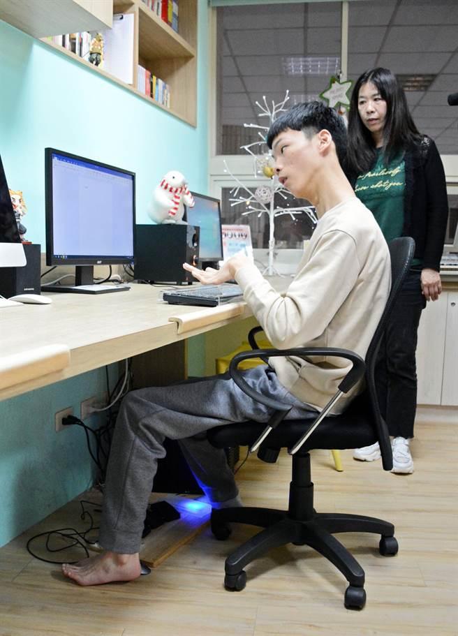屏大新鮮人蔡東霖(左)手腳並用透過電腦溝通,母親王淑萍則在一旁協助生活瑣事。(林和生攝)
