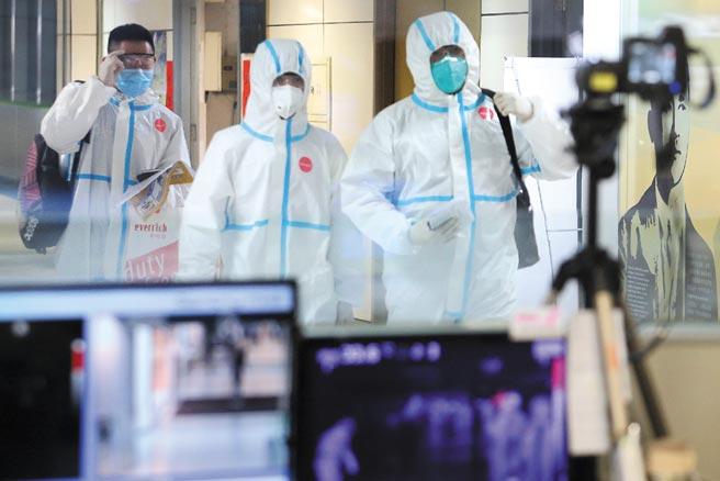 專家擔憂若不及時採取強而有力的防疫手段,一旦變種病毒散播速度加快,感染人數大增,恐擊潰當地醫療資源。圖為桃園機場第二航廈入境管制區內,3名身穿防護衣的旅客,正通過發燒篩檢站。(范揚光攝)