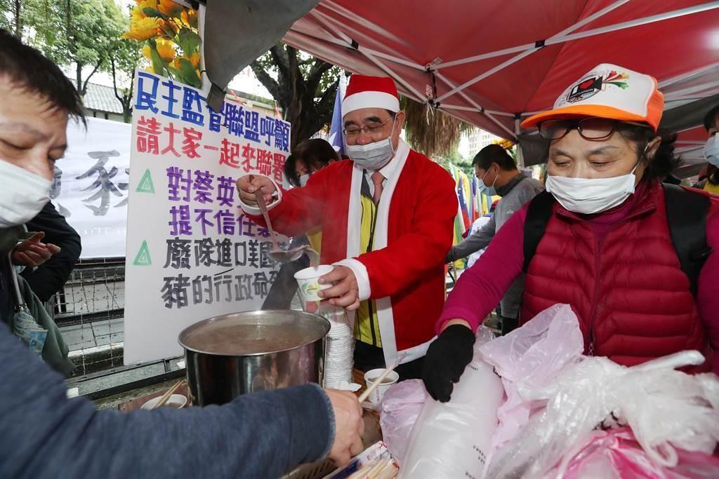 穿著聖誕老公公衣帽的新黨主席吳成典(中)24日帶領新黨議員潘懷宗等人在立法院大門口,告訴民眾,最後一碗豬肝湯的意義。吳成典舀起最後一碗沒有萊劑的豬肝湯,分送給在現場反萊豬進口的聲援民眾。(劉宗龍攝)