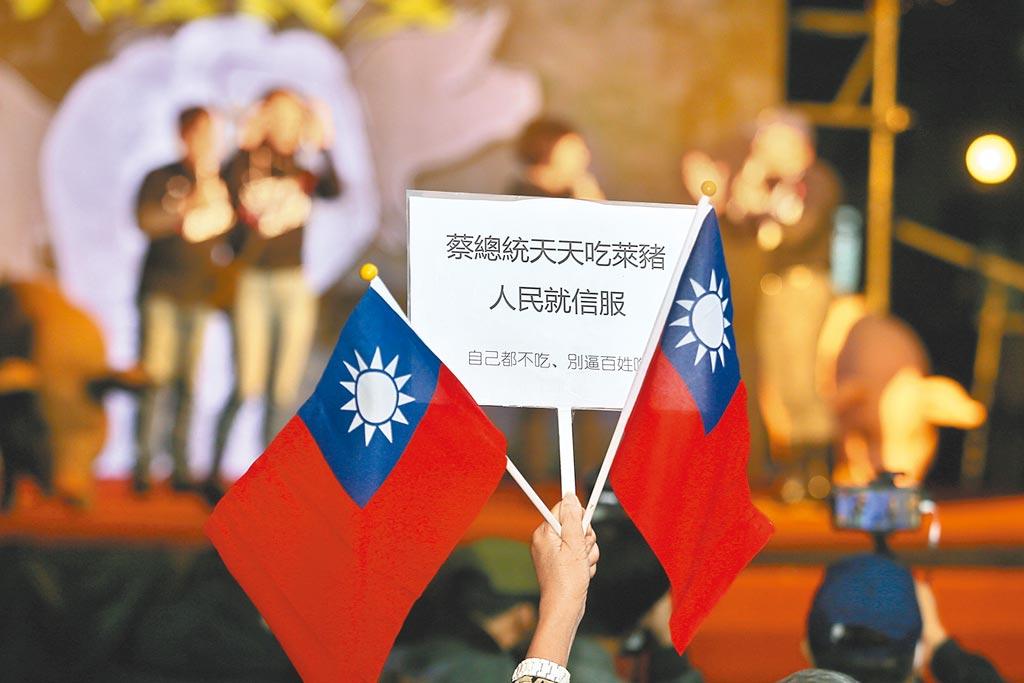 國民黨23日舉辦「守護食安之夜」,許多民眾自發前來參與,其中有民眾高舉「蔡總統天天吃萊豬人民就信服」手牌。(杜宜諳攝)
