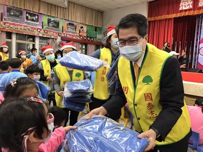 國泰世華銀行基金會董事長李明賢親手送禮物,祝福孩童們耶誕快樂。(國泰提供)