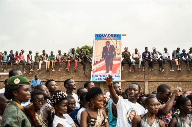 中非共和國首都班吉的競選活動上,民眾手執競選海報聽取現任總統圖瓦德拉的演講。該國將於12月27日進行總統選舉第一輪投票。(圖/新華社)