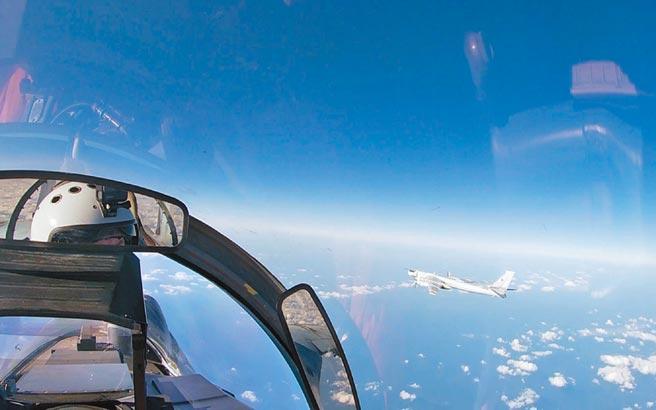 俄羅斯蘇-35戰機飛行員望向其護航的解放軍空軍轟-6K轟炸機。(影片截圖自俄羅斯國防部)