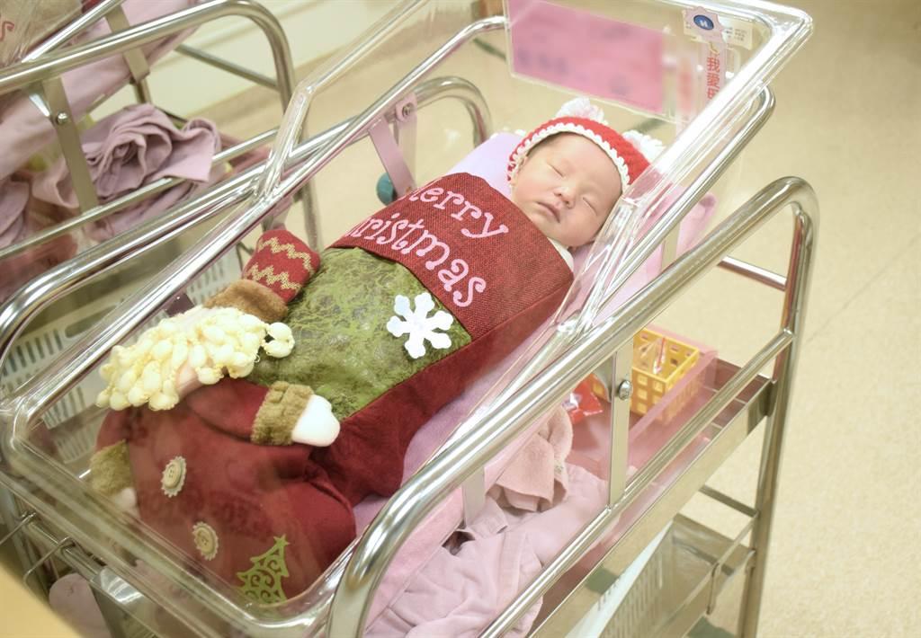 亞東醫院為剛出生的寶寶們穿上可愛聖誕裝,每個寶寶在嬰兒床上戴上聖誕帽,身體套進聖誕襪裡,模樣相當可愛。(圖/亞東醫院提供)