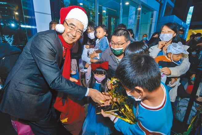 中信投信董事長陳國世(左一)發送糖果給小朋友,讓大朋友小朋友歡慶耶誕佳節。(中信銀行提供)