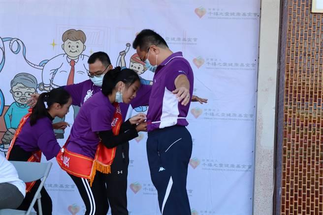 台南市佳里區仁愛國小舉行64周年校慶活動,學童幫校長楊宗穎(右)量腰圍。(劉秀芬攝)