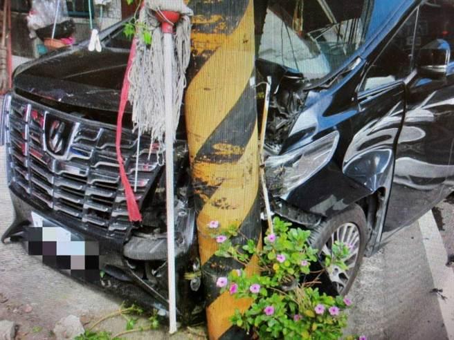 停在路邊的黑色休旅車遭撞後,往前撞到電線桿,車頭毀損。(圖/讀者提供)