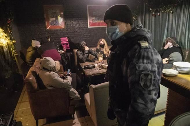 在全球疫情嚴重程度排名第4的俄羅斯,26日新增29258人確診、567人病歿,累計病例超過302萬例、逾5.4萬人死亡。圖為莫斯科警方前往酒吧突襲臨檢,查看顧客與店家是否確實遵守防疫規定。(美聯)