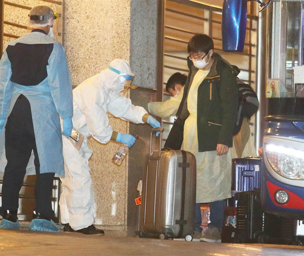 檢疫所工作人員仔細將旅客行李擦拭消毒液,做到防疫無缺失。(陳怡誠攝)