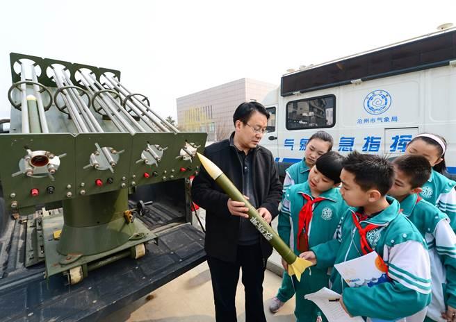 河北滄州市氣象台工作人員(左一)向滄州市實驗小學的學生們介紹人工增雨發射設備。(圖/新華社)