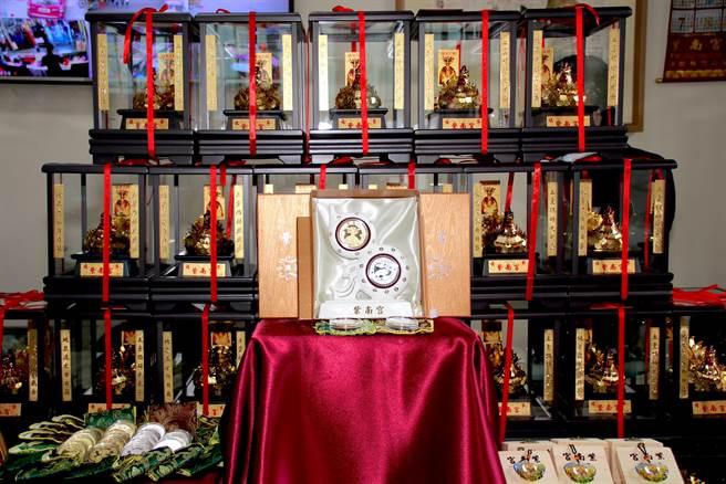 紫南宮盒裝葫蘆錢母套幣,白色葫蘆陶瓷基座上鑲有兩枚套幣,一面有土地公像,另一面則刻有伏地牛,象徵招財吉祥。(民眾提供/黃立杰南投傳真)