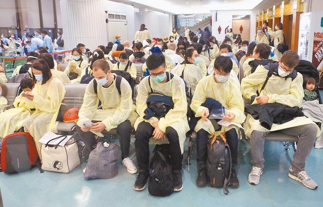 從英國抵台的旅客,下機後被引導前往A7內候機室,由國境疾管人員審核集中檢疫通知書,及健康聲明暨檢疫通知書內容,完成檢疫申報。(陳麒全攝)