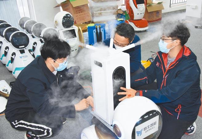 陸國企混改基金落地,將聚焦核心領域,圖為青島高新區一科技司技術人員在調試二代消毒機器人。 (新華社)