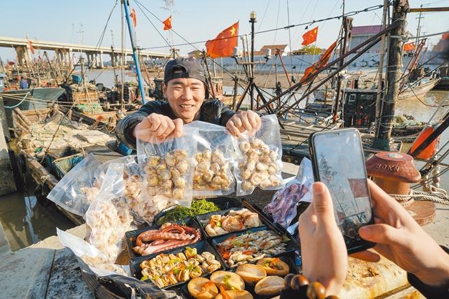 4月22日,民眾在江蘇省連雲港市贛榆區朱蓬口漁港,拍短片推銷海產。(新華社)