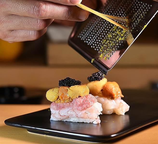 超級握壽司〈海鮮四重奏〉的食材在醋飯上「疊」好後,〈忻鮨〉主廚會再現刨日本愛知縣柚子皮屑增益香氣。(圖/姚舜)