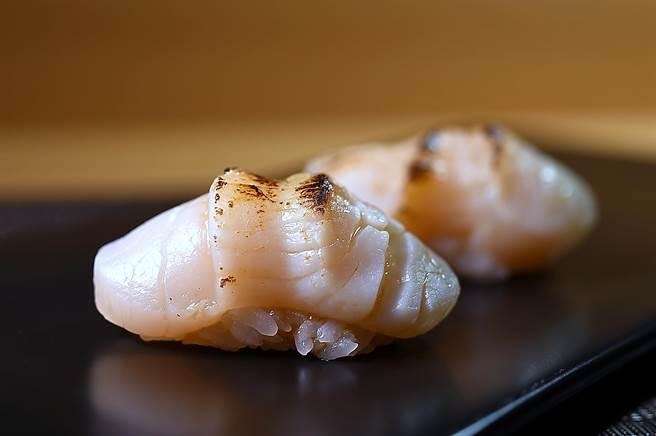 傳統干貝要生長三年才採收,〈忻鮨〉的〈炙燒北海道干貝握壽司〉所用干貝是二年生,肉質較軟嫩,炙燒後表面有焦香。(圖/姚舜)