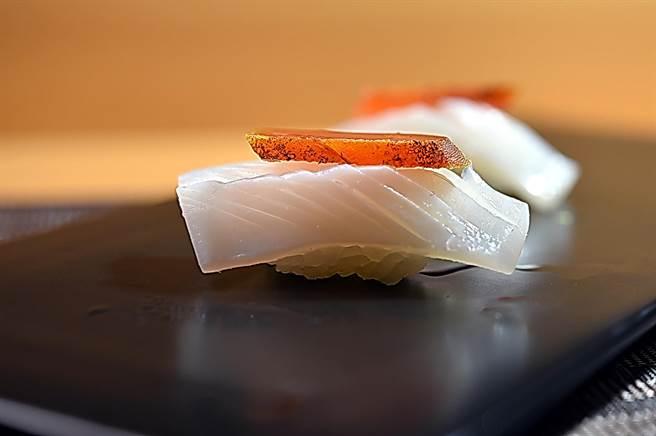 〈忻鮨〉的〈澎湖軟絲握壽司〉用了主廚袁育銓丈母娘在屏東自製的烏魚子提味。(圖/姚舜)