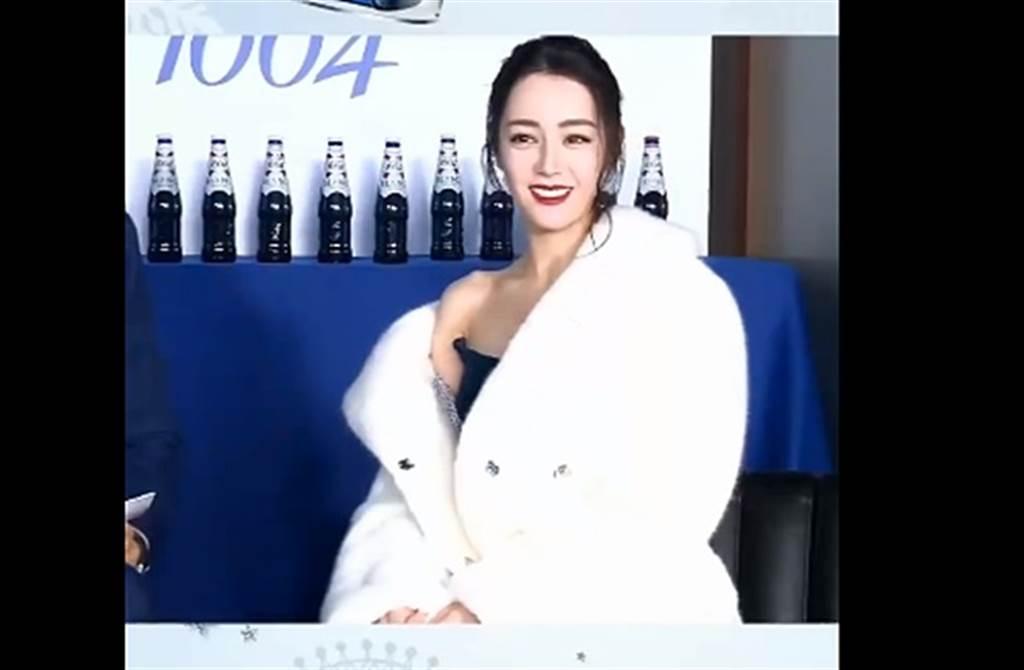 迪丽热巴身披白大衣不时滑落。 (取自微博)