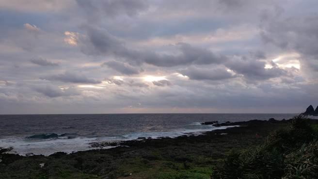 蘭嶼第1道曙光,因為東清段海灘上空雲層過厚,原先預期6時33分該出現的曙光仍躲在厚雲裡,20分鐘過後,人群離開,僅剩數名遊客留在海邊時,皇天不負苦心人,厚雲逐漸散開,些微光束漸漸透出雲層映射出來,讓特別前來蘭嶼等待曙光的遊客興奮不已。(民眾提供/蔡旻妤台東傳真)