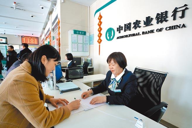 大陸國有大行持續在市場購買美元。圖為中國農業銀行行員為客戶辦理業務。 (新華社)