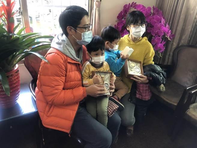碰巧是1月2日生的苗栗媽媽(右),帶著雙胞胎到竹山參拜,幸運獲得精裝錢母套幣;廟方特別加碼送雙胞胎一人一組葫蘆套幣,模樣逗趣可愛。(竹山紫南宮提供/黃立杰南投傳真)