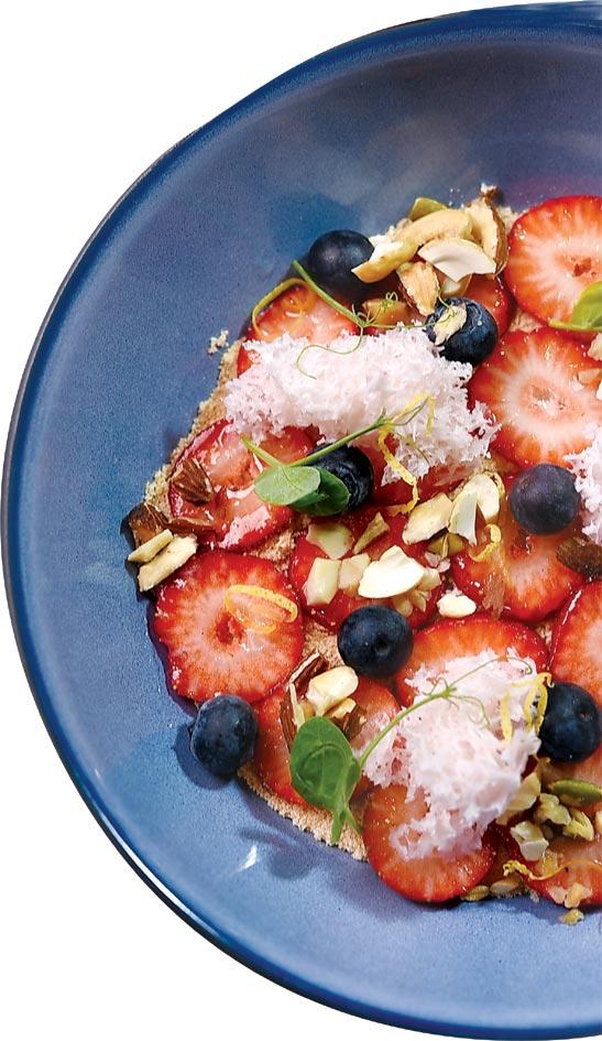 〈草莓馬丁尼〉創作靈感源自於葡萄牙著名甜點〈米糠布丁〉,主廚先以自製草莓醬鋪底,再疊上打發鮮奶油、灑餅乾碎,最後鋪上新鮮草莓片、藍莓與優格微波蛋糕,再撒上杏仁堅果碎粒,成品有如小花園。圖/姚舜