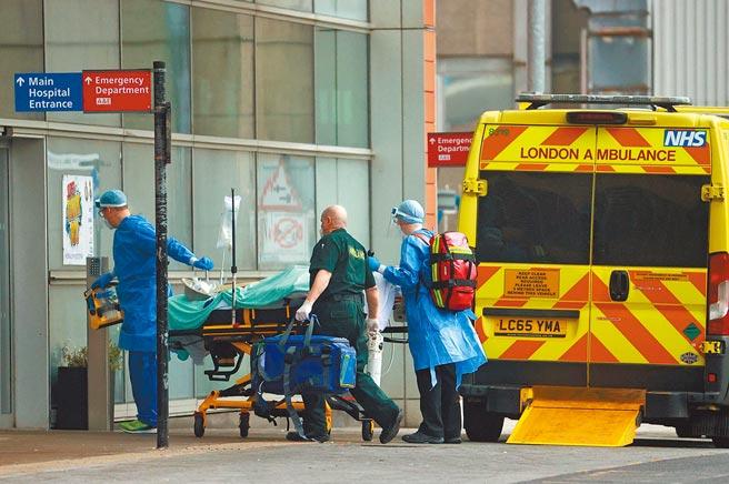 倫敦皇家醫院外,醫護人員正將1名病患送進醫院治療。英國新冠疫情嚴峻,政府已決重啟野戰醫院收治病患。(路透)