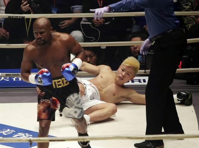 2018年跨年夜,退役拳王梅威瑟(左)在表演賽擊倒日本格鬥選手那須川天心。(美聯社資料照)