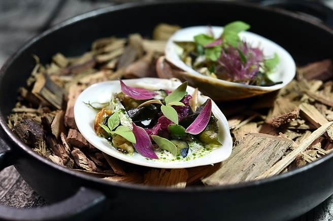 〈炭火〉這道菜是以直火炭烤的蛤蠣、赤嘴蛤與海瓜子等3種貝類,搭配醃漬海藻與藍莓,並用蒔蘿油搭蛤蠣醬汁提。(圖/姚舜)