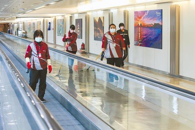 疫情嚴峻,桃園機場第二航廈入境長廊,清潔人員定時定點在做消毒工作。(陳麒全攝)