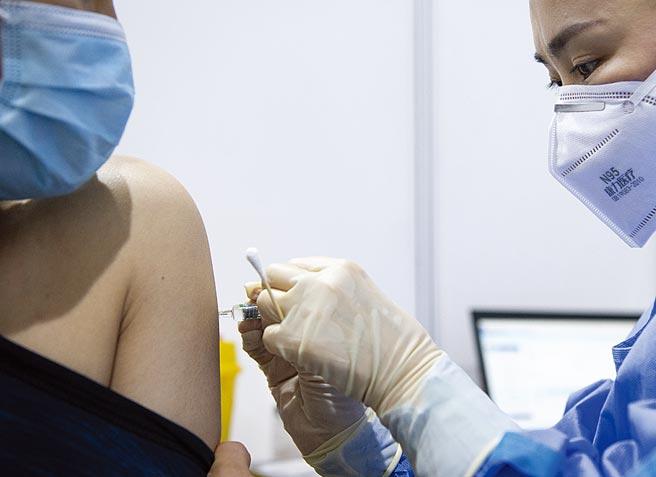 廈門台商協會拔得頭籌,4日通知在廈門的18至59歲台胞向協會登記,本周就可施打第一劑。圖為醫護人員在設置於北京市朝陽區朝陽規畫藝術館的臨時接種點為接種人員注射疫苗。(中新社)