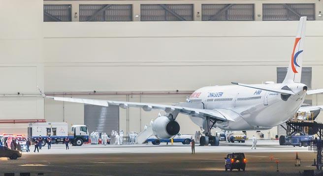 2020年2月3日,東航載送的台商首班武漢返台包機飛抵桃園機場。專案小組全副武裝在飛機維修公司廠棚為旅客辦理檢疫消毒與入關程序。(本報系資料照片)