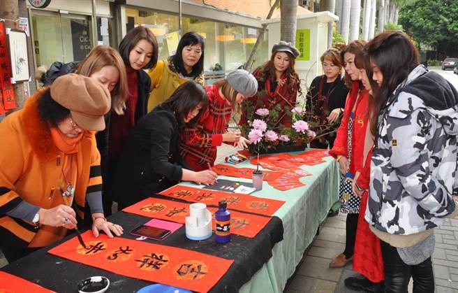 學生現場揮毫及彩繪,讓春聯及紅包袋獨具風格。(謝瓊雲攝)
