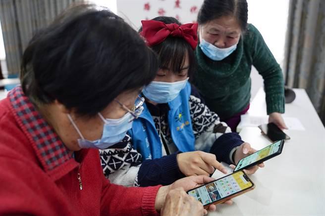 老人手機被犯罪集團不良廠商植入木馬程式扣款,陸600萬受害者被竊18億。圖為北京教首老年人使用手機。(圖/新華社)